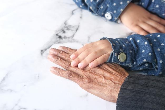 テーブルの上で年配の女性の手を握っている子供の女の子の詳細ショット
