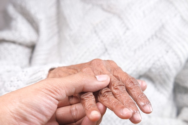 고위 여자의 손을 잡고 젊은 남자의 상세 샷
