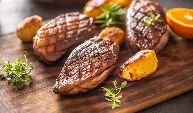 Detail of tasty roasted duck breasts and potatoes on a wooden cutting board.