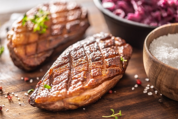 Detail of tasty roasted duck breasts and stewed red cabbage on a wooden cutting board.