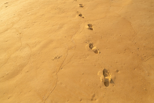 모래의 세부 질감 휴가에 휴식을 위한 바다 태양 해변 모래에 발 인쇄와 화창한 여름 배경 푸켓 태국에서 아름 다운 해변입니다.