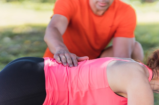 Detail of a trainer's hand on the back of a woman correcting exercise posture in a park.