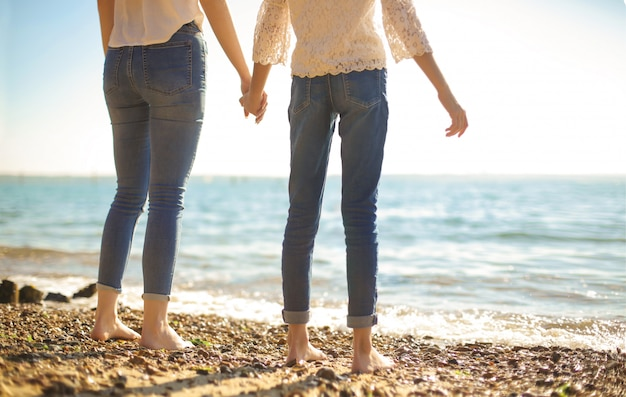 Detail of two girls holding each other hand while staring the horizon