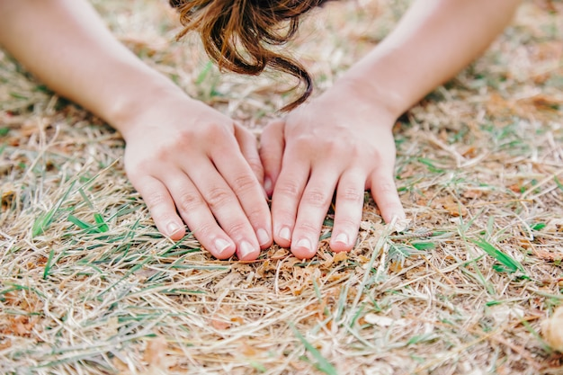 Detail of unrecognizable woman hands palms touching the earth ground. human contact with nature concept. environmental issues and healthy lifestyle. mindfulness way of life.