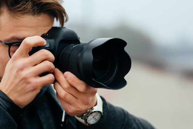 Detail view of young man in eyeglasses taking photos on the street.