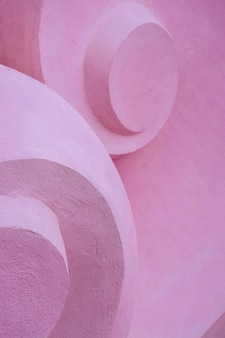 Detail of volume stone sculpture with twirl shapes. pink concrete convex background