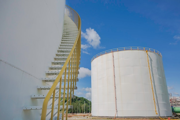 Detail of white tanks oil in tank farm with iron staircase