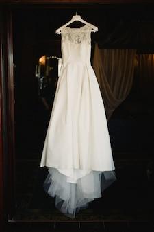 Detail of a white wedding dress hanging.