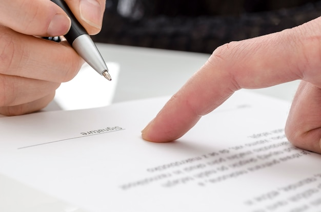 Detail of a woman signing a paper. male finger showing where to sign.