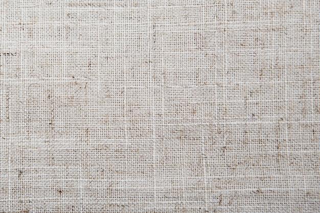 詳細なクローズアップヴィンテージ古い織り目加工の生地黄麻布、黄褐色の素朴な