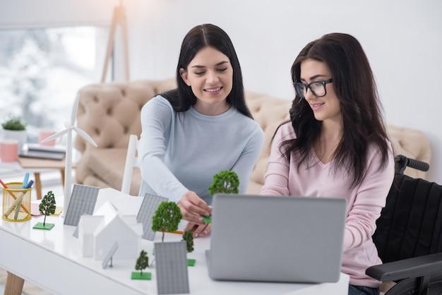 詳細なモデリング。ツリーモデルを見ながらラップトップを使用して楽観的な不動の女性と同僚