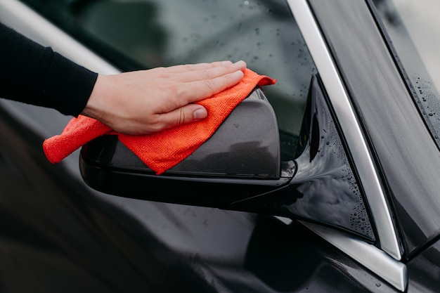 Detailed shot of mans owner hand wiping side mirror of black car with microfiber cloth. cleanliness and car care concept