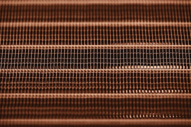 Detailed texture engine water cooling radiator with horizontal lines.   orange automobile part with copyspace close up.