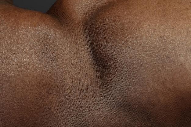 인간 피부의 상세한 질감. 젊은 아프리카 계 미국인 남성 몸의 총을 닫습니다. 스킨 케어, 바디 케어, 건강 관리, 위생 및 의학 개념. 아름다움과 잘 보존되어 보입니다. 피부과.