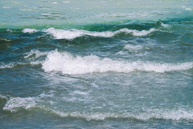 Подробная текстура бирюзовой мчащейся водной поверхности. пороги горной реки заделывают.