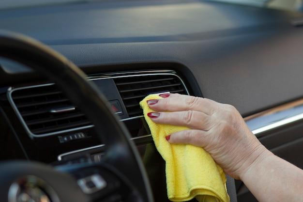 布で車内の掃除と磨きの詳細成熟した女性労働者の手は布で