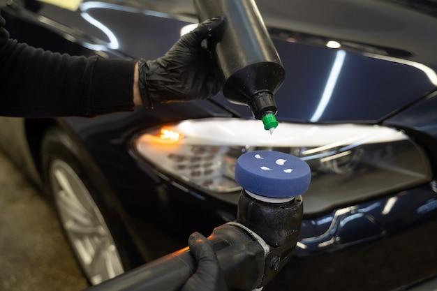 Мастер детализации наносит на полировальную машинку пасту для автомобильной полировки.