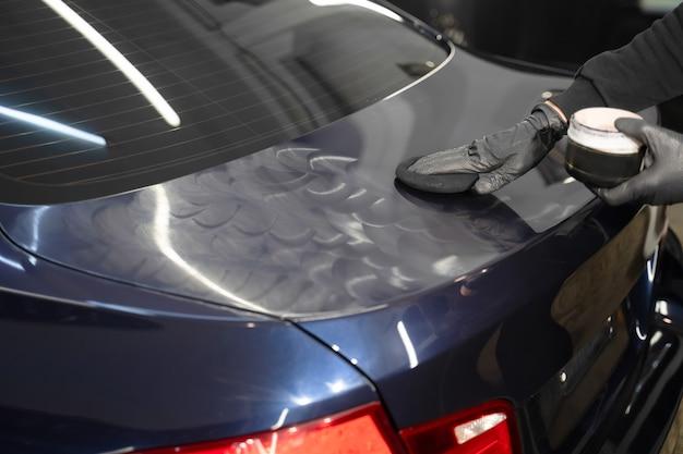 Detailing master applies polishing wax to the car body.