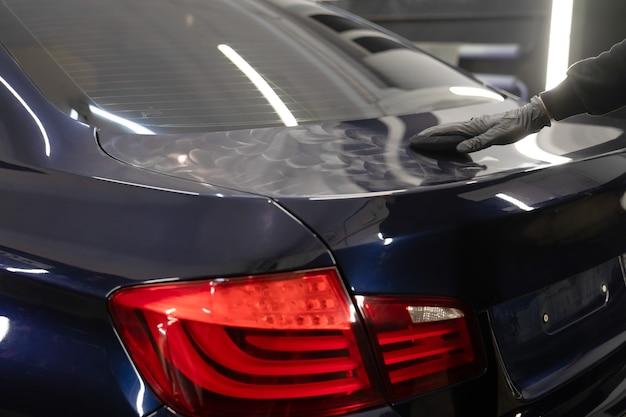 Мастер по детализации наносит на кузов автомобиля полировальный воск.