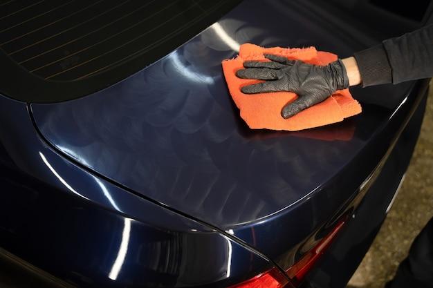 Мастер по детализации наносит воск для полировки кузова автомобиля.