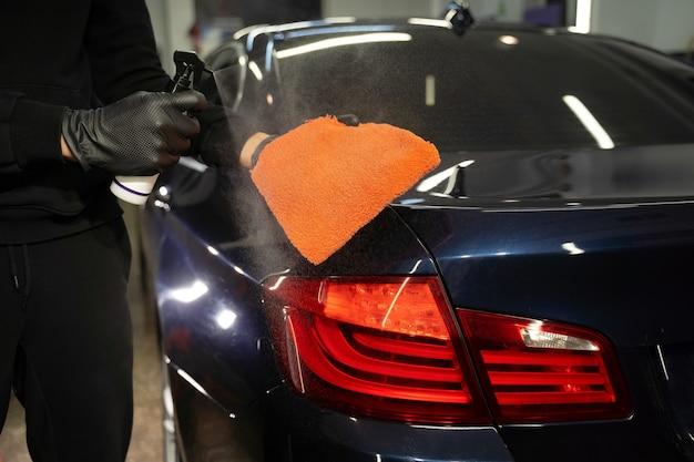 Detailing master sprays the produc on rag.