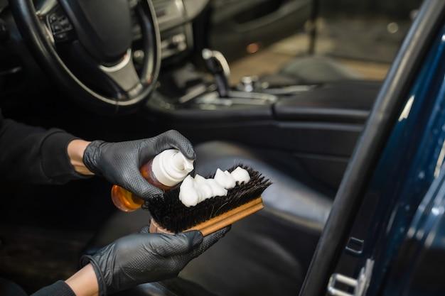 Монтажник наносит на щетку пену для чистки кожи.