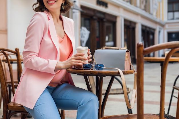 Dettagli di accessori di bella donna in abito elegante seduto in caffè, occhiali da sole, borsetta, colori rosa e blu, tendenza moda primavera estate, stile elegante, umore romantico, vacanza in europa,