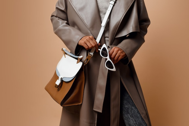 Details. black woman wearing grey leather coat , posing on beige background. brown bag and white sunglasses in hands.  autumn or winter fashion concept.