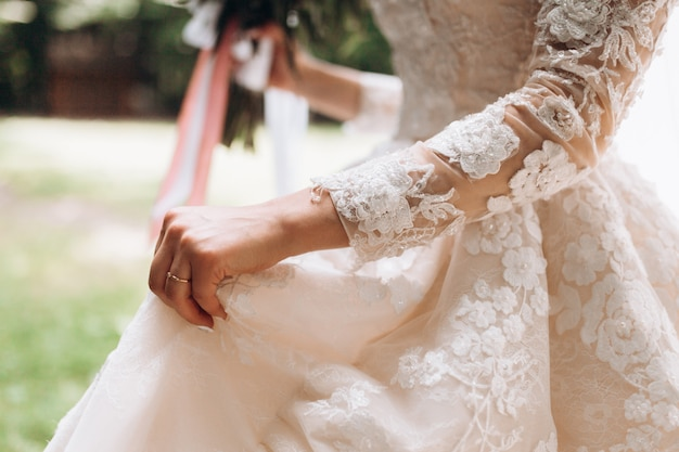 Details of bridal wedding dress, hand with wedding ring outdoors