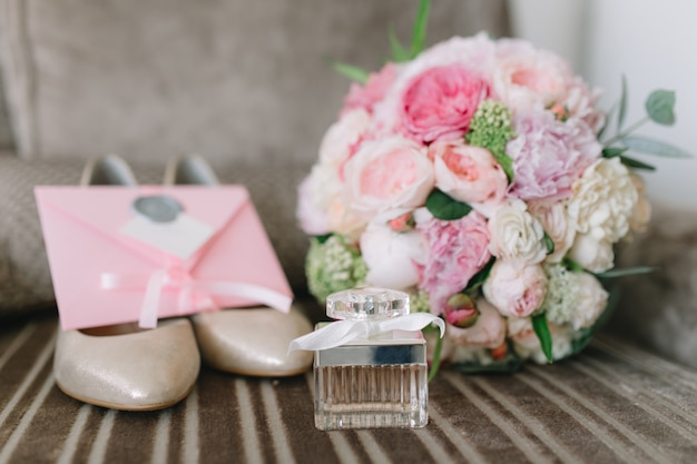 Details of the bride: shoes, pink bouquet, perfumes and invitations.