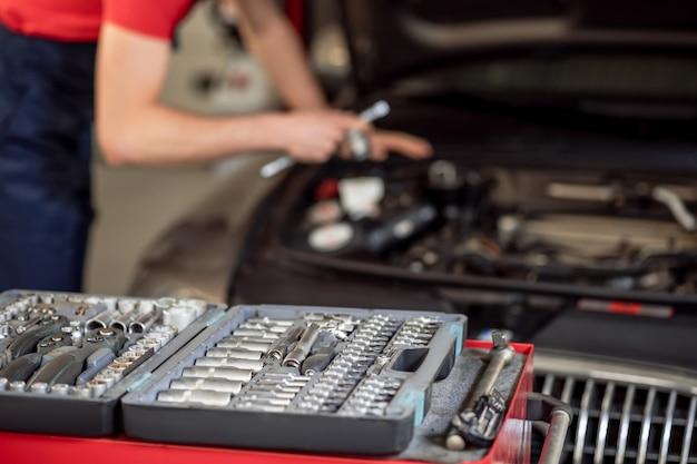 詳細、車。金属部品を備えたオープンケースで、自動車整備士の後ろで車のボンネットの近くで作業しています