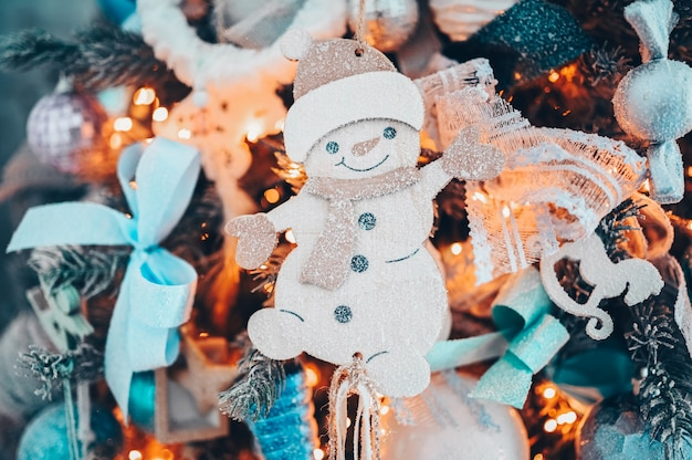 Details of a christmas decorated tree in dark turquoise and orange colors with toy snowman