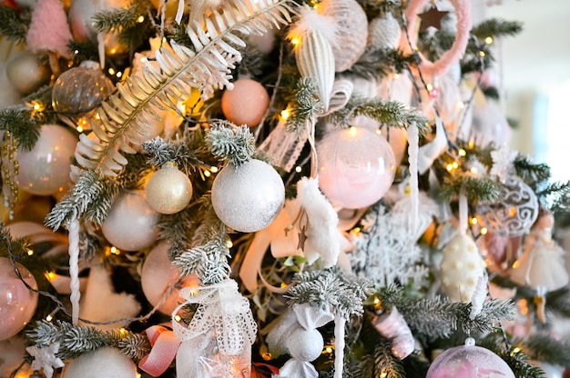 Details of a christmas decorated tree in soft pink colors.