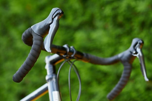詳細は、緑の自然の背景にロードバイクのハンドルバーのショットをクローズアップ