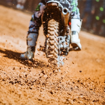 Details of flying debris during an acceleration with mountain bikes race in dirt track in sunshine day