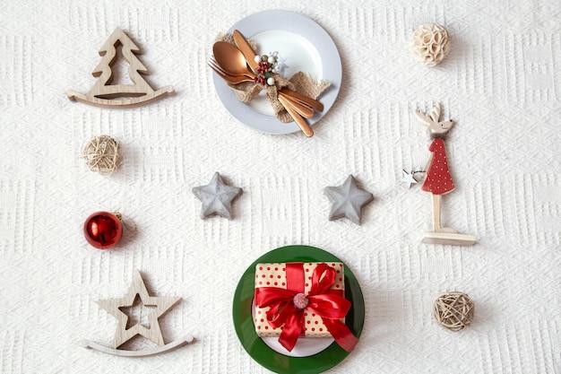 白い背景の上のクリスマステーブル設定の詳細をクローズアップ。