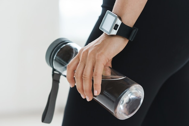 Details of modern sport and workout. female hand with smartwatch holding reusable bottle with water.