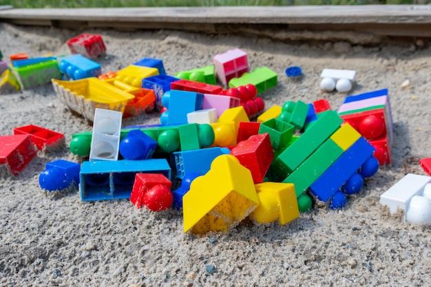 砂の上に置かれた子供たちのマルチカラーのプラスチック構造の詳細。雨上がりに濡れた遊び場で子供たちに忘れられた梨