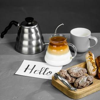 灰色のテーブルでの朝食の詳細。コーヒー、長い注ぎ口のあるティーポット、お菓子、そしてこんにちはの碑文が書かれたカード。フィルタードリッパーでコーヒーを淹れる。コーヒーを作る別の方法。