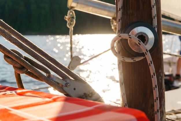 Подробная информация о парусной лодке на размытом фоне блестящей воды