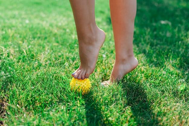 긴장을 풀기 위해 뾰족한 고무 노란색 공에 발끝으로 서 있는 젊은 여성의 맨발에 대한 세부 정보...
