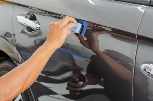 車の詳細。男性の整備士が店の車にガラスセラミックコーティングを施しています。