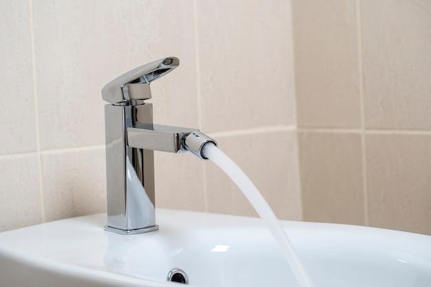 Детали белого керамического биде с водой из крана в современной ванной комнате с бежевой плиткой