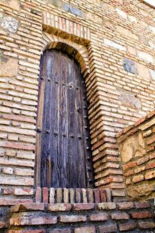 Детали, старая деревянная дверь в алькасаба, малага, испания