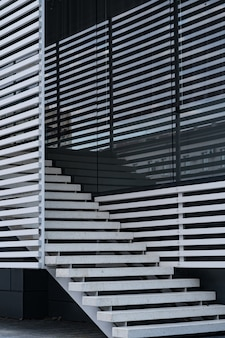 Details of railing and stairs of a modern building and shadow reflection on windows