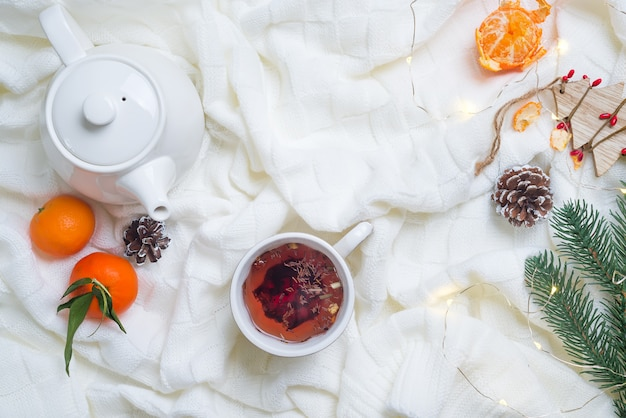 Details of still life in the home interior, cup of tea with tangerines on knitted white wa