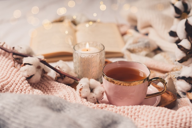 Details of still life in the home interior of living room. sweater, cup of tea, cotton, cozy, book, candle