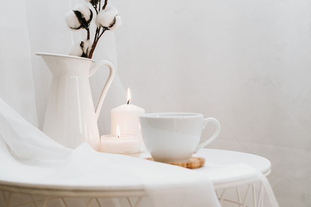 Details of still life in the home interior of living room on white . cup of coffee, cotton, candle, vase. moody. copy space for text