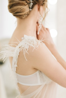 The details of the wedding day. the gown of the bride dress with feathers close-up