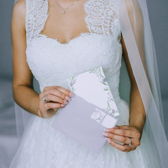 Details of a wedding dress. close up of faceless girl in beautiful white wedding dress holding an envelope with a blank postcard. bride's accessories. morning of the bride.